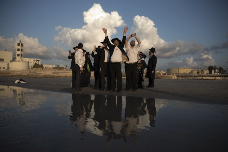 Ultra-orthodox Jews gesture at a Tel Aviv beach after emptying their pockets during the Jewish New Year ritual of Tashlich, October 2, 2014. Tashlich is a ritual of casting away sins of the past year into the water ahead of Yom Kippur, the Jewish Day of Atonement, which starts at sundown Friday. (Finbarr O'Reilly/Reuters)