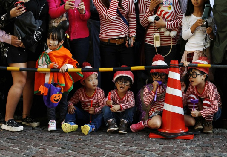 Spectators, dressed in costumes, wait for a Halloween parade in Kawasaki, south of Tokyo, October 26, 2014. More than 100,000 spectators turned up to watch the parade, where 2,500 participants dressed up in costumes, according to the organizer. (Yuya Shino/Reuters)