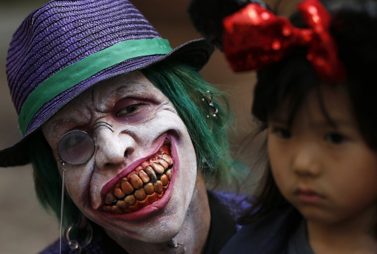 A participant in costume pose next to a girl before a Halloween parade in Kawasaki, south of Tokyo, October 26, 2014. More than 100,000 spectators turned up to watch the parade, where 2,500 participants dressed up in costumes, according to the organizer. (Yuya Shino/Reuters)