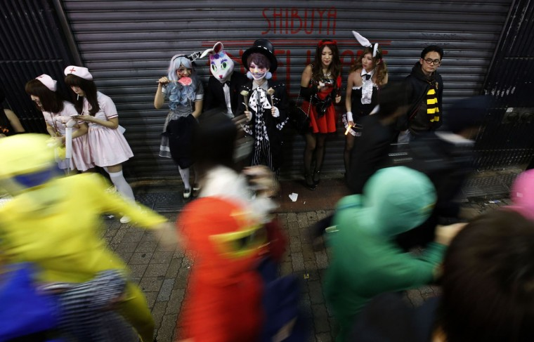Participants, wearing make-up and costumes, eat candy during Halloween night in Tokyo's Shibuya district October 31, 2014. Thousands of costumed revelers descended on Shibuya crossing in downtown Tokyo on Friday to celebrate Halloween in what has in recent years become a incredibly popular Japanese past time. (Yuya Shino/Reuters)