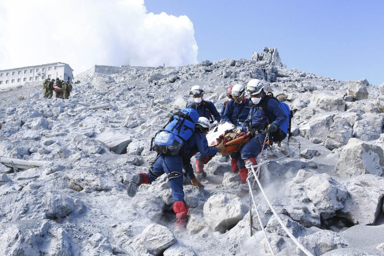 Firefighters carry a hiker during rescue operations near the peak of Mount Ontake, which straddles Nagano and Gifu prefectures, central Japan, in this handout photograph released by the Tokyo Fire Department. The death toll from a Japanese volcano eruption rose to 47 on Wednesday, the worst in 88 years, after more victims were discovered on the ash-covered mountain. (Tokyo Fire Department/Handout via Reuters)