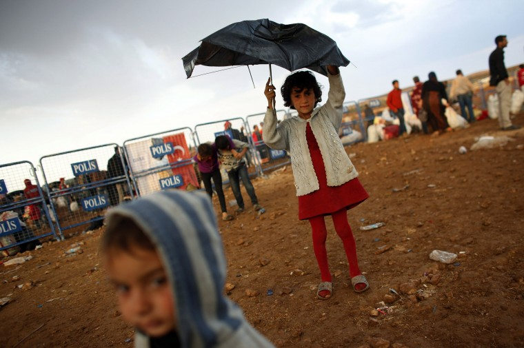 Syrian Kurdish refugee children play in the rain after crossing into Turkey from the Syrian border town Kobani, near the southeastern Turkish town of Suruc in Sanliurfa province October 2, 2014. More than 150,000 refugees have fled Kobani over the past two weeks alone, with a steady exodus continuing. Officials from Turkey's AFAD disaster management agency said some 4,000 crossed on Wednesday, and a similar figure the day before. (Murad Sezer/Reuters)