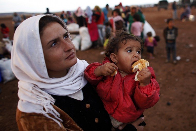 A Syrian Kurdish refugee woman with her daughter waits for transportation after crossing into Turkey from the Syrian border town Kobani, near the southeastern Turkish town of Suruc in Sanliurfa province October 2, 2014. More than 150,000 refugees have fled Kobani over the past two weeks alone, with a steady exodus continuing. Officials from Turkey's AFAD disaster management agency said some 4,000 crossed on Wednesday, and a similar figure the day before. (Murad Sezer/Reuters)
