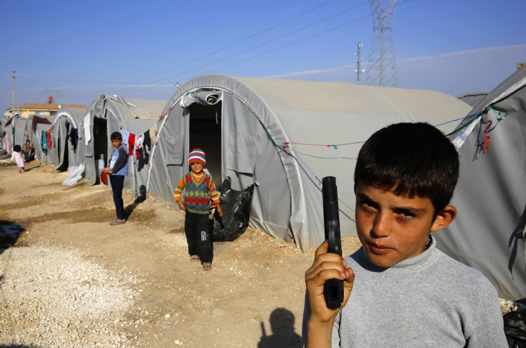 A young Kurdish refugee from Kobani holds a toy pistol at a Kurdish refugee camp in the border town of Suruc, Sanliurfa province October 27, 2014. (Yannis Behrakis/Reuters)