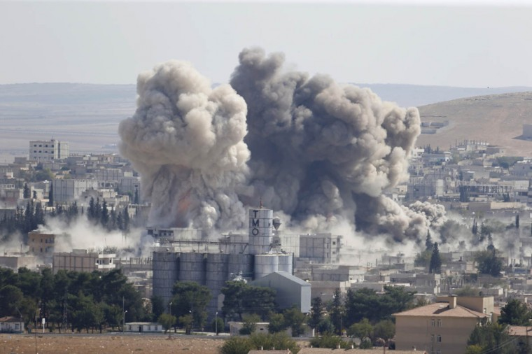 Smoke rises after an U.S.-led air strike in the Syrian town of Kobani Ocotber 8, 2014. U.S.-led air strikes on Wednesday pushed Islamic State fighters back to the edges of the Syrian Kurdish border town of Kobani, which they had appeared set to seize after a three-week assault, local officials said. The town has become the focus of international attention since the Islamists' advance drove 180,000 of the area's mostly Kurdish inhabitants to flee into adjoining Turkey, which has infuriated its own restive Kurdish minority-- and its NATO partners in Washington -- by refusing to intervene. (Umit Bektas/Reuters photo)