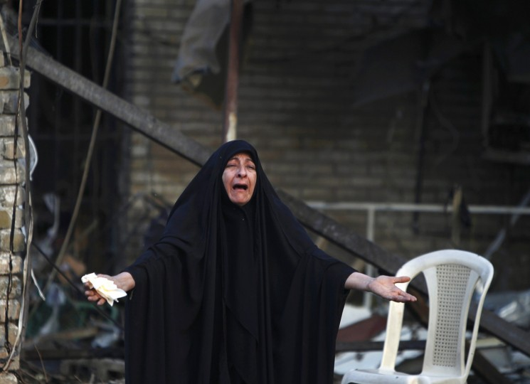 A woman reacts at the site of Tuesday's car bomb attack, at the entrance to the neighbourhood of Kadhimiya in Baghdad, October 15, 2014. The suicide car bombing killed a parliament member and 24 others in the Shi'ite neighborhood in Baghdad, according to police and medical officials, as Islamic State attacked towns in western Anbar province. (Ahmed Saad/Reuters)
