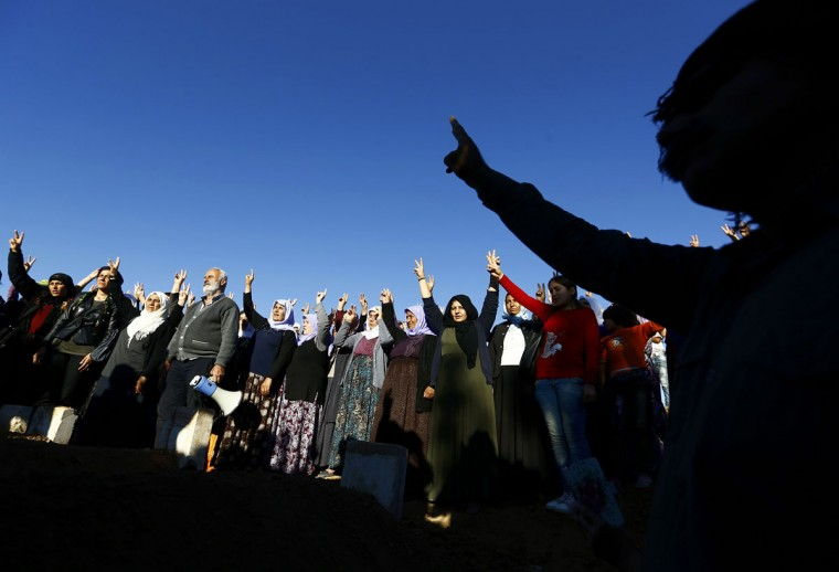 Turkish Kurdish women show victory sign during the funeral of Kurdish fighters killed during clashes against Islamic State in Kobani, at a cemetery in the southeastern town of Suruc, Sanliurfa province October 21, 2014. Turkey has offered to help Kurds enter the fight for Kobani, parts of which have apparently been re-taken from Islamic State militants, while the U.S. has air-dropped arms for the first time to help the city's defenders. (REUTERS/Kai Pfaffenbach)