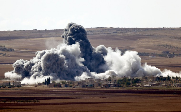 Smoke rises from a village on the outskirts of the Syrian town of Kobani, seen from near the Mursitpinar border crossing on the Turkish-Syrian border in the southeastern town of Suruc in Sanliurfa province October 15, 2014. American-led forces conducted 21 airstrikes near Kobani, Syria, in the last two days to slow the advance of Islamic State militants, the U.S. military said on Tuesday, warning the situation on the ground is fluid as militants try to gain territory. (REUTERS/Kai Pfaffenbach)