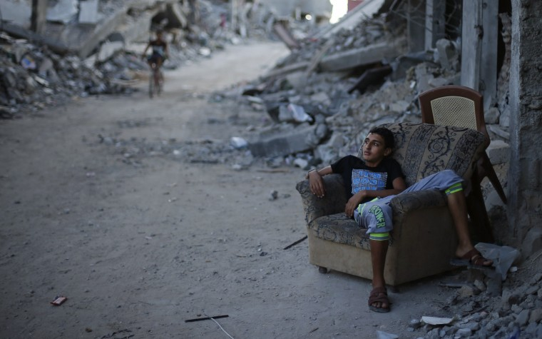 A Palestinian boy sits on a couch outside his house, which witnesses said was destroyed during the seven-week Israeli offensive, in the east of Gaza City October 2, 2014. (Suhaib Salem/Reuters)