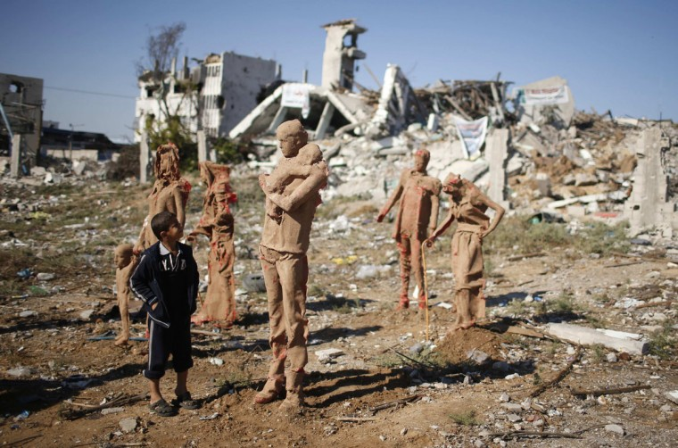 A Palestinian boy looks at statues that are made of fiberglass and covered with clay by Palestinian artist Eyad Sabbah, which are depictions for the Palestinians who fled their houses from Israeli shelling during the most recent conflict between Israel and Hamas, in the east of Gaza City October 21, 2014. (REUTERS/Mohammed Salem)