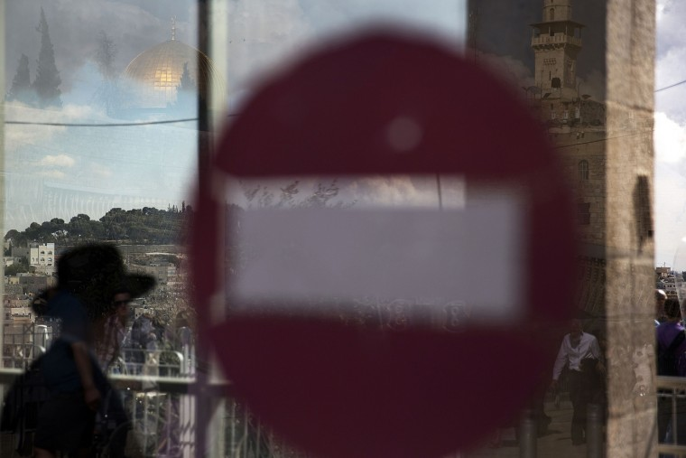 The golden Dome of the Rock (top L) is reflected in a window with a no entry sign near the Western Wall in Jerusalem's Old City October 30, 2014. Israeli police on Thursday shot dead a 32-year-old Palestinian man suspected of having tried hours earlier to kill a far-right Jewish activist, leading to fierce clashes in East Jerusalem and fears of a new Palestinian uprising. The Al-Aqsa compound, or Temple Mount, which is a central cause of the latest violence, was closed to all visitors as a security precaution. It was the first full closure of the site, venerated by both Jews and Muslims, in 14 years. REUTERS/Finbarr O'Reilly
