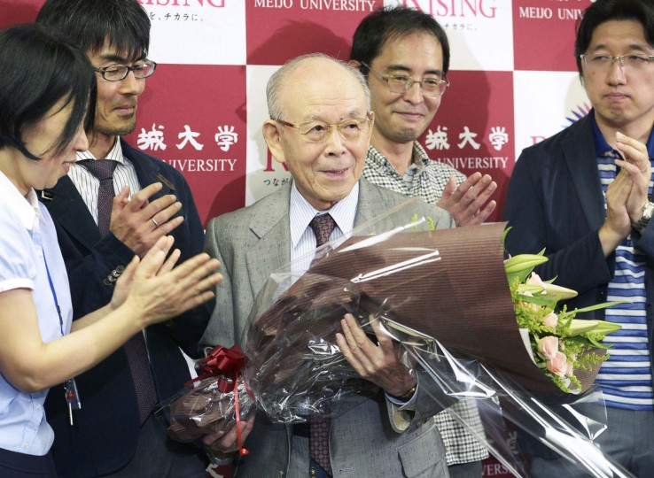Meijo University professor Isamu Akasaki (C) is presented with a bouquet of flowers from his laboratory staff members during a news conference at Meijo University in Nagoya, central Japan, in this photo taken by Kyodo October 7, 2014. Japanese scientists Akasaki and Hiroshi Amano and American Shuji Nakamura won the 2014 Nobel prize for Physics for inventing a new energy efficient and environmentally friendly light source, the LED, the award-giving body said on Tuesday. Mandatory credit (REUTERS/Kyodo)