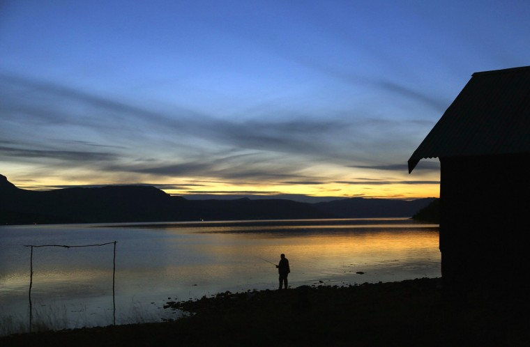 A man casts his fishing line in Bals-Fiord, north of the Arctic Circle, near the village of Mestervik in northern Norway September 30, 2014. (Yannis Behrakis/Reuters)