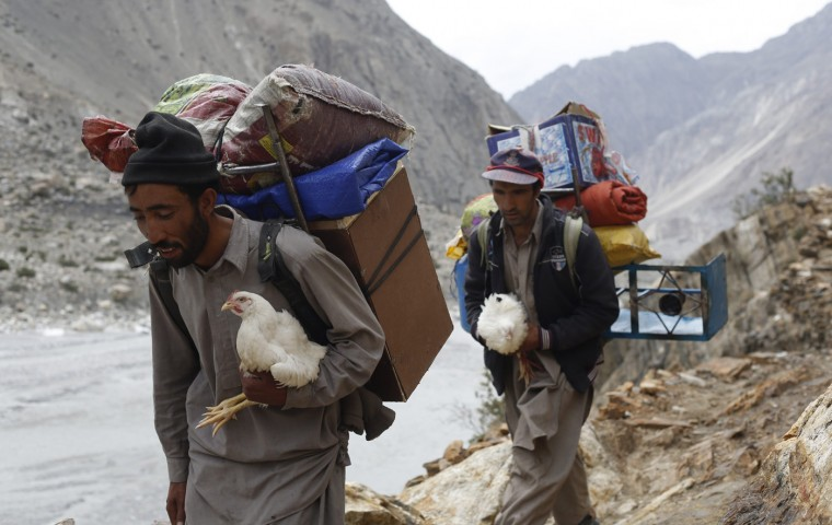 Porters carry live chickens, which serve as meat supplies, during a K2 base camp trek in the Karakoram mountain range in Pakistan August 28, 2014. A local porter receives 700 Pakistani Rupee ($6.8) per day and usually carries 25kg. Owners of mules can earn three times as much, as their animals carry 75kg. (Wolfgang Rattay/Reuters)