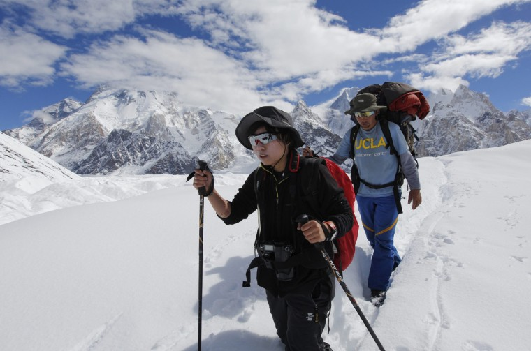 A porter guides his trekking client, 26-year old Yvonne Yip (L), from Hong Kong down the Baltoro glacier in the Karakoram mountain range in Pakistan September 7, 2014. (Wolfgang Rattay/Reuters)