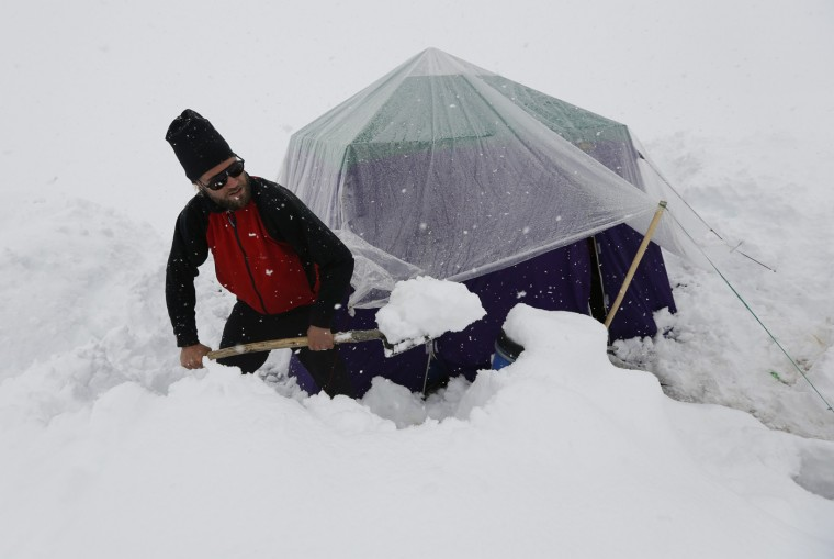 A German trekker removes snow from a kitchen tent at Concordia, the confluence of the Baltoro and Godwin-Austen glaciers, near the world's second highest mountain K2 (8,611 meters) in the Karakoram mountain range in Pakistan September 5, 2014. While other parts of Pakistan and northern India were flooded, Concordia in the Karakoram mountain range was covered with a seasonally unusual amount of snow. (Wolfgang Rattay/Reuters)
