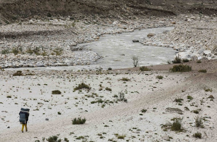 A porter carries his load as he walks along a glacial river during a K2 base camp trek, near the resting point of Paju in the Karakoram mountain range in Pakistan September 10, 2014. A local porter receives 700 Pakistani Rupee ($6.8) per day and usually carries 25kg. Owners of mules can earn three times as much, as their animals carry 75kg. (Wolfgang Rattay/Reuters)