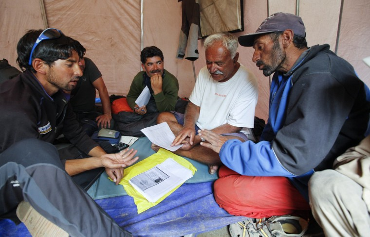 Porters talk with guide Altaf Hussain (2nd R) and Mujeeb Ur-Rahman (C) in the village of Askole in the Karakoram mountain range in Pakistan September 11, 2014. A local porter receives 700 Pakistani Rupee ($6.8) per day and usually carries 25kg. Owners of mules can earn three times as much, as their animals carry 75kg. (Wolfgang Rattay/Reuters)