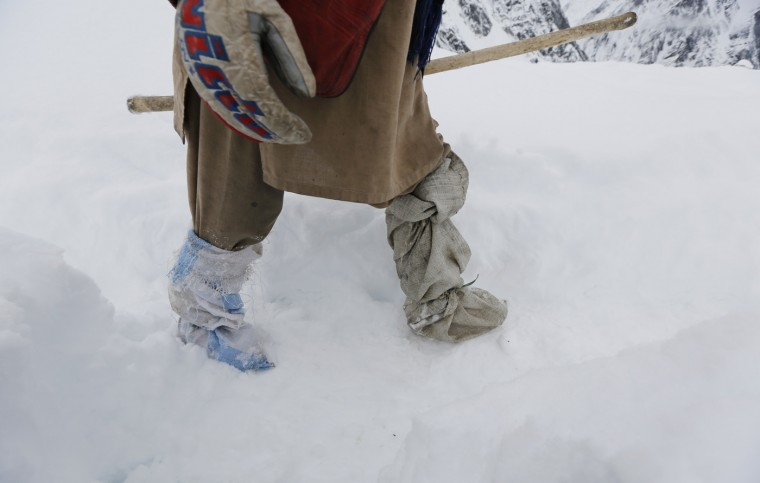 A porter leaves the snow-covered Concordia, the confluence of the Baltoro and Godwin-Austen glaciers, wearing self-made gaiters near K2 in the Karakoram mountain range in Pakistan September 6, 2014. While other parts of Pakistan and northern India were flooded, Concordia in the Karakoram mountain range was covered with a seasonally unusual amount of snow. (Wolfgang Rattay/Reuters)