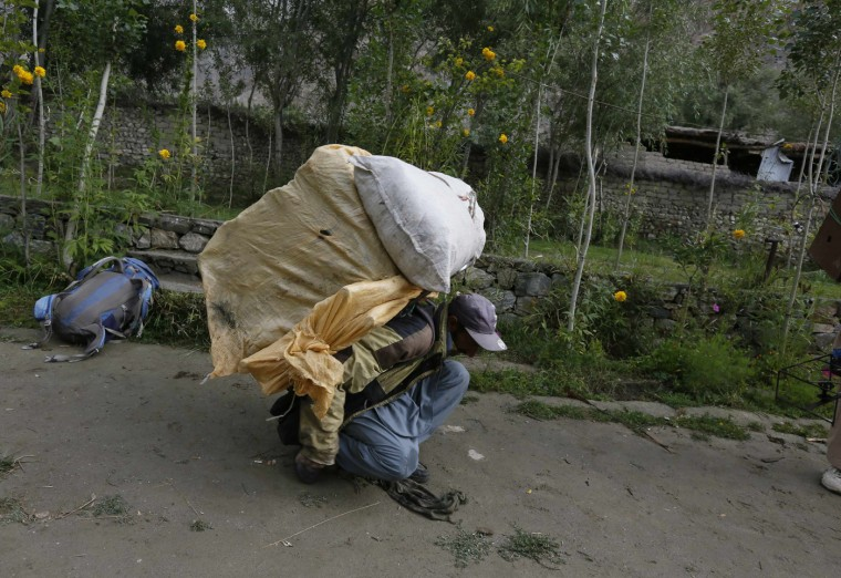 Porter Hassan Trampa, 35, lifts his load in the village of Askole in the Karakoram mountain range in Pakistan August 28, 2014. A local porter receives 700 Pakistani Rupee ($6.8) per day and usually carries 25kg. Owners of mules can earn three times as much, as their animals carry 75kg. (Wolfgang Rattay/Reuters)