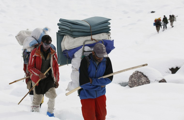 Porters make their way through deep snow on the Baltoro glacier in the Karakoram mountain range in northern Pakistan September 8, 2014. While other parts of Pakistan and northern India were flooded, Concordia in the Karakoram mountain range was covered with a seasonally unusual amount of snow. (Wolfgang Rattay/Reuters)