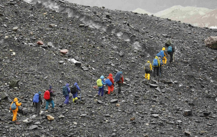A group of Pakistani soldiers carry their guns uphill along the K2 base camp trek in the Karakoram mountain range in Pakistan September 8, 2014. While other parts of Pakistan and northern India were flooded, Concordia in the Karakoram mountain range was covered with a seasonally unusual amount of snow. (Wolfgang Rattay/Reuters)