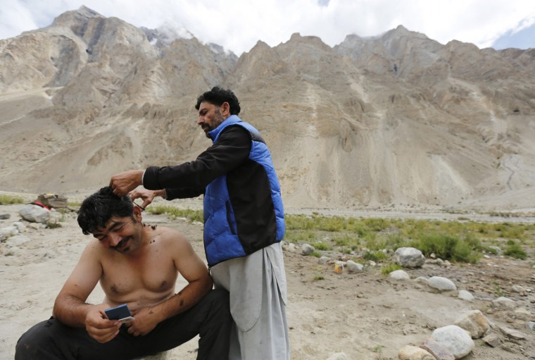 Mountain guide Mujeeb Ur-Rahman, 38, receives a haircut from cook Shukrullah Baig, 52, at Bardoumal along the K2 base camp trek in the Karakoram mountain range in Pakistan August 29, 2014. (Wolfgang Rattay/Reuters)