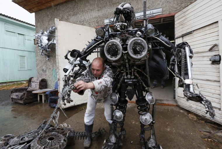 "Mechanic and welder Sergei Kulagin, 32, tests the ""Alien Samurai"", an electro-mechanical mobile robot made by Kulagin using car components, outside an automobile repair workshop in the town of Divnogorsk outside Krasnoyarsk, Siberia, October 15, 2014. Enthusiast Kulagin, who works as a mechanic of an automobile service station, created about twenty sculptures made of used car parts and components during his non-working hours. (REUTERS/Ilya Naymushin)"