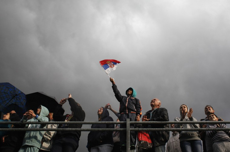 An attendee waves a Serbian flag during a military parade to mark 70 years since the city's liberation by the Red Army in Belgrade October 16, 2014. Serbia feted Russia's Vladimir Putin with troops, tanks and fighter-jets on Thursday to mark seven decades since the Red Army liberated Belgrade, balancing its ambitions of European integration with enduring reverence for a big-power ally deeply at odds with the West. (Djordje Kojadinoviic/Reuters