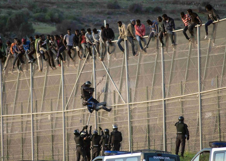 A Spanish Civil Guard pulls an African migrant from a border fence, as Spanish Civil Guard officers stand underneath, during an attempt to cross into Spanish territories, between Morocco and Spain's north African enclave of Melilla October 15, 2014. Around 300 migrants attempted to cross the border into Spain and about 3 managed to pass the fence and are currently held at CETI, the short-stay immigrant centre, according to local authorities. (REUTERS/Jesus Blasco de Avellaneda)