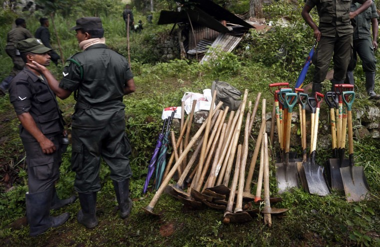 Members of a military rescue team stand near stacks of shovels and hoes at the site of a landslide at the Koslanda tea plantation near Haldummulla October 30, 2014. Hopes of finding survivors under the mud and rubble of a landslide in south-central Sri Lanka had run out by first light on Thursday, though a government minister cut the estimated death toll to more than 100 from 300 the previous night. REUTERS/Dinuka Liyanawatte