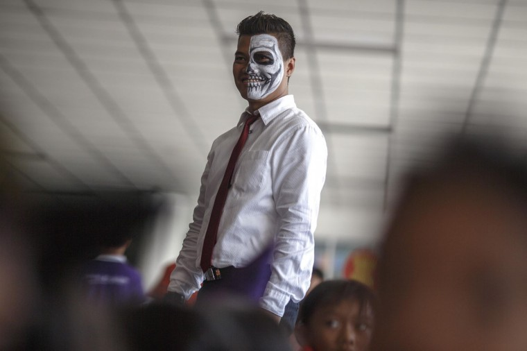 A teacher with his face painted attends a halloween party at a school in Bangkok October 31, 2014. (Athit Perawongmetha/Reuters)