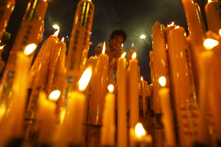 A devotee lights candles at a Chinese shrine during the annual vegetarian festival in Bangkok late September 24, 2013. The festival celebrates the local Chinese community's belief that abstinence from meat and various stimulants during the ninth lunar month of the Chinese calendar will help them obtain good health and peace of mind. (Athit Perawongmetha/Reuters)