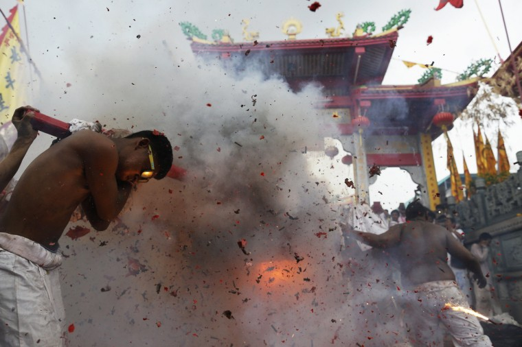 Firecrackers explode as devotees of the Chinese Jui Tui Shrine return the statue to the shrine after a procession celebrating the annual vegetarian festival in Phuket September 30, 2014. (Damir Sagolj/Reuters)
