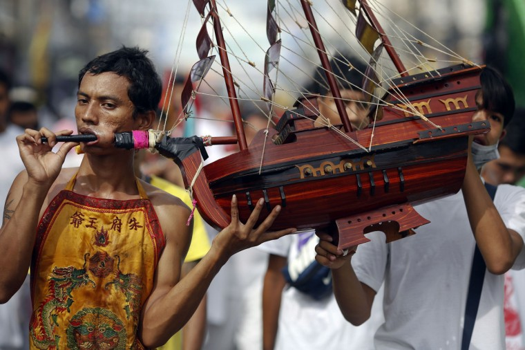 A devotee of the Chinese Jui Tui Shrine is assisted while carrying a model of a ship pierced through his cheek during a procession celebrating the annual vegetarian festival in Phuket September 30, 2014. (Damir Sagolj/Reuters)