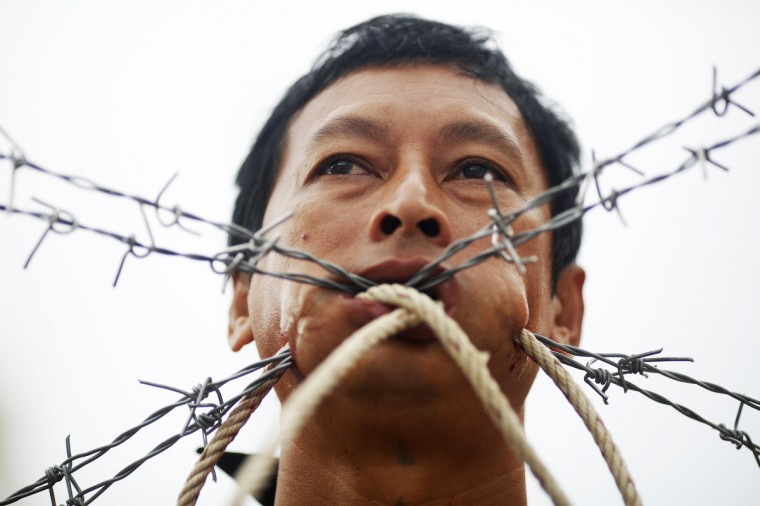 Barbed wire and ropes are pierced through the cheeks of a devotee of the Chinese Jui Tui Shrine during a procession celebrating the annual vegetarian festival in Phuket September 30, 2014. (Damir Sagolj/Reuters)