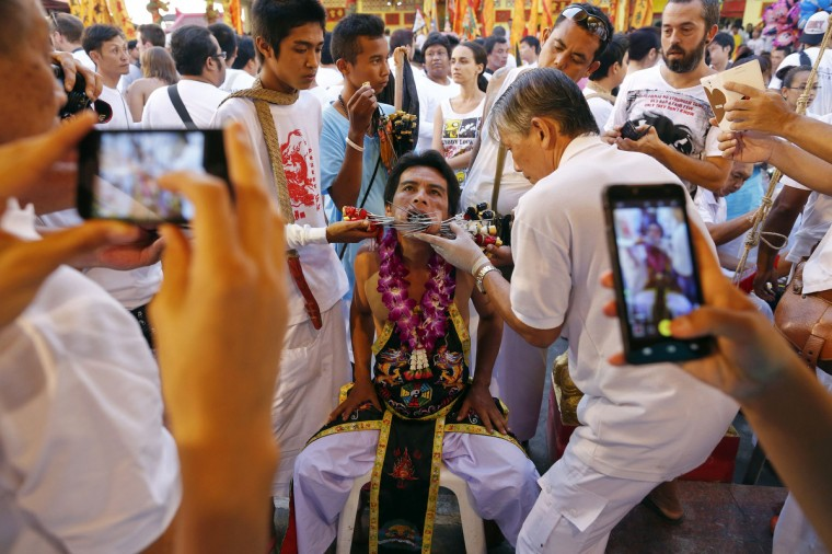 People take pictures as a devotee of the Chinese Bang Neow Shrine is helped to insert more spikes through his cheeks before a procession celebrating the annual vegetarian festival in Phuket September 29, 2014. (Damir Sagolj/Reuters)