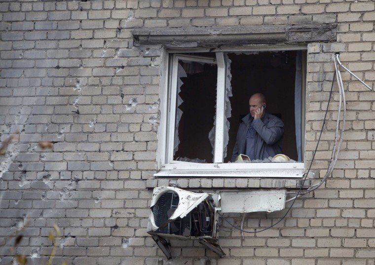 A man talks on a phone as he is seen through a window broken by recent shelling in Donetsk, eastern Ukraine, October 16, 2014. (Shamil Zhumatov/Reuters)