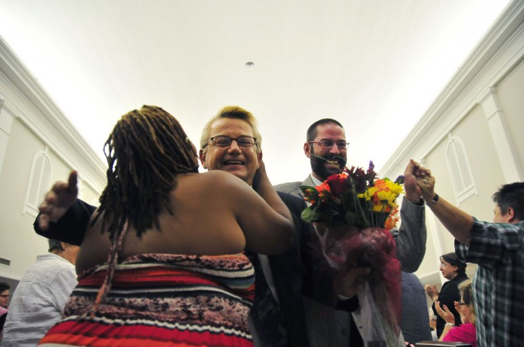 Newlyweds Bo Bass (C) and Kenny Wright embrace friends as they walk down the aisle at Mayflower Congregational Church in Oklahoma City, Oklahoma October 6, 2014. Dozens of gay and lesbian couples jumped into action on Monday in Virginia, Oklahoma, Utah, Wisconsin and Indiana after the Supreme Court rejected appeals in gay marriage cases in those five states. (REUTERS/Nick Oxford)