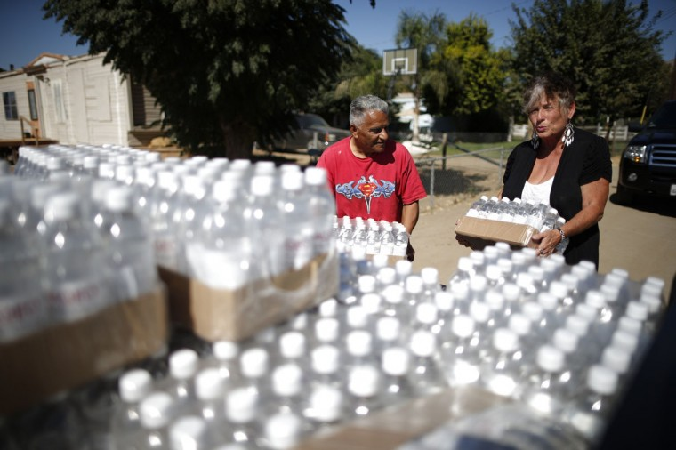 Donna Johnson, 70, (R) lifts pallets of donated bottled water from the back of her truck during her daily delivery run to residents whose wells have run dry, with resident Ruben Perez, 68, in Porterville, California October 14, 2014. In one of the towns hardest hit by California's drought, the only way some residents can get water to flush the toilet is to drive to the fire station, hand-pump water into barrels and take it back home. The state's three-year drought comes into sharp focus in Tulare County, the dairy and citrus heart of the state's vast agricultural belt, where more than 500 wells have dried up. (Lucy Nicholson/Reuters)