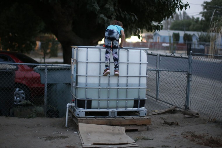 Abigail Beltran, 6, whose family's well has run dry, climbs on a water storage tank in her front yard in Porterville, California October 14, 2014. In one of the towns hardest hit by California's drought, the only way some residents can get water to flush the toilet is to drive to the fire station, hand-pump water into barrels and take it back home. The state's three-year drought comes into sharp focus in Tulare County, the dairy and citrus heart of the state's vast agricultural belt, where more than 500 wells have dried up. (Lucy Nicholson/Reuters)