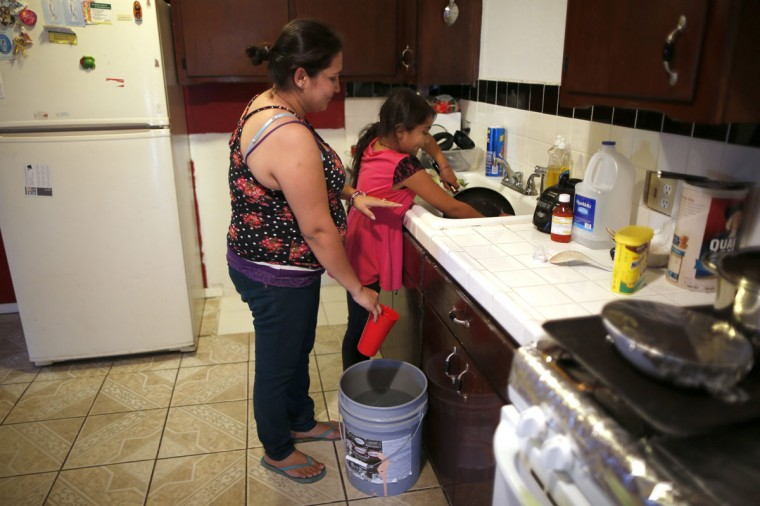 Marisela Corona, 26, (L) whose well has run dry, washes dishes with her daughter Andrea Andrade Corona, 8, from a water bucket in Porterville, California October 14, 2014. In one of the towns hardest hit by California's drought, the only way some residents can get water to flush the toilet is to drive to the fire station, hand-pump water into barrels and take it back home. The state's three-year drought comes into sharp focus in Tulare County, the dairy and citrus heart of the state's vast agricultural belt, where more than 500 wells have dried up. (Lucy Nicholson/Reuters)