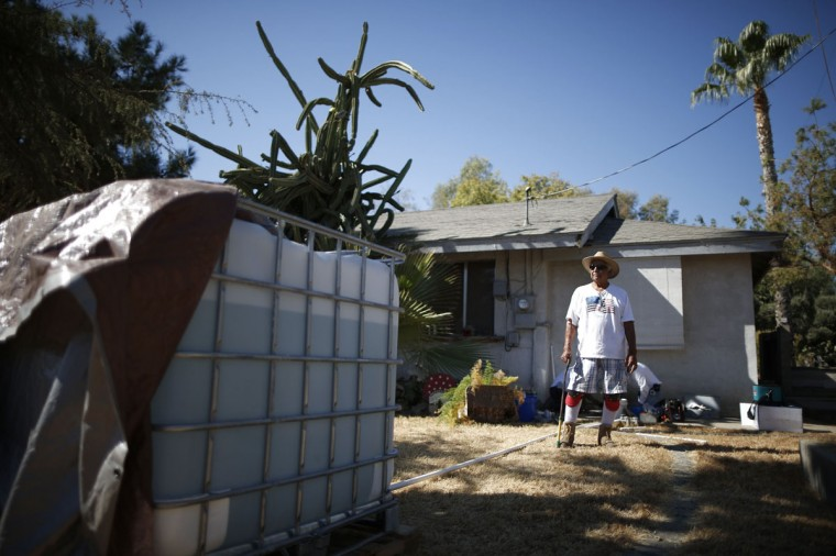 Manuel Rodriguez, 83, watches as workmen install a water pump to carry water from an outdoor container into his home in Porterville, California October 14, 2014. In one of the towns hardest hit by California's drought, the only way some residents can get water to flush the toilet is to drive to the fire station, hand-pump water into barrels and take it back home. The state's three-year drought comes into sharp focus in Tulare County, the dairy and citrus heart of the state's vast agricultural belt, where more than 500 wells have dried up. (Lucy Nicholson/Reuters)