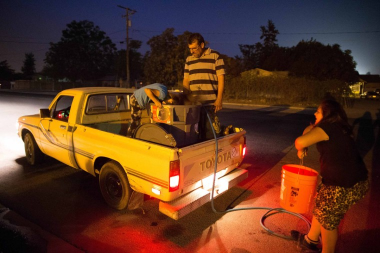 Macario Beltran, 41, (C) a mechanic whose family's well has run dry, fills containers in his truck with water from the fire station, with his daughters Abigail, 6, (L) and Denika, 10, in Porterville, California October 14, 2014. In one of the towns hardest hit by California's drought, the only way some residents can get water to flush the toilet is to drive to the fire station, hand-pump water into barrels and take it back home. The state's three-year drought comes into sharp focus in Tulare County, the dairy and citrus heart of the state's vast agricultural belt, where more than 500 wells have dried up. (Lucy Nicholson/Reuters)