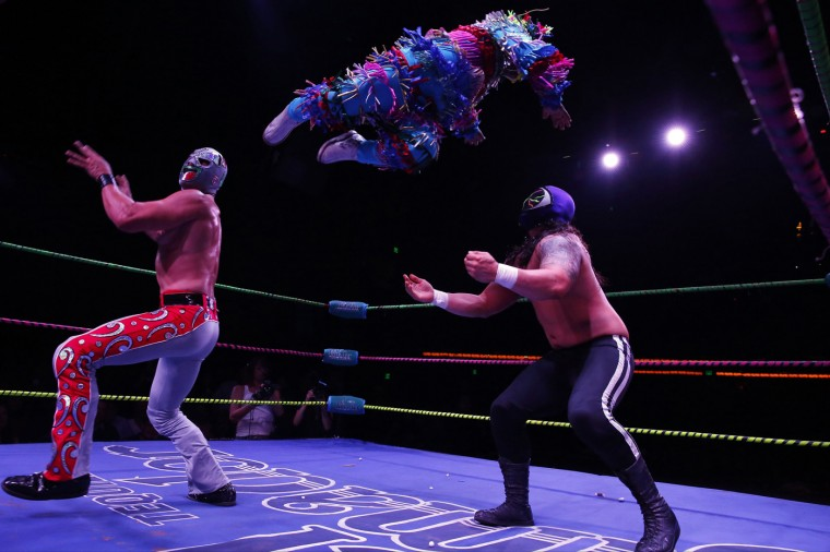 "Lucha libre wrestler Mariachi Loco (L) launches Pinatita through the air at Ojo Del Mal while fighting during the Lucha VaVoom ""Night of the Vampire"" performance in Los Angeles, California October 29, 2014. REUTERS/Patrick T. Fallon"