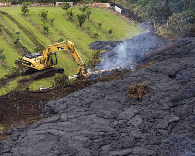 A construction crew tries to contain the lava flow from Mount Kilauea in Pahoa, Hawaii October 29, 2014. The slow-moving river of molten lava from the erupting Kilauea volcano crept over residential and farm property on Hawaii's Big Island on Wednesday after incinerating an outbuilding as it threatened dozens of homes at the edge of the former plantation town. REUTERS/Marco Garcia