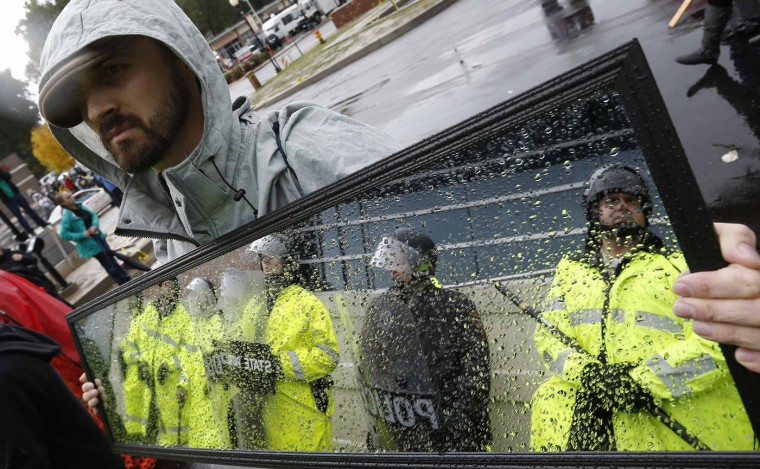 Police officers are reflected in a mirror held by a protestor during a demonstration at the Ferguson Police Department in Ferguson, Missouri, October 13, 2014. Hundreds of protesters converged in the pouring rain on the Ferguson, Missouri, police department on Monday as they launched another day of demonstrations over the August killing by police of an unarmed black teenager. (Jim Young/Reuters)