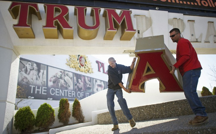(L-R) Steven Nordaby and Tony Demidio, of Calvi Electric, remove the letter 'A' from the signage of Trump Plaza Casino in Atlantic City, New Jersey October 6, 2014. Workers began removing the large letters spelling out the Trump name from the shuttered Trump Plaza casino in Atlantic City on Monday after real-estate mogul Donald Trump sued to end a licensing deal that allowed the casino owners to use his name. Trump, who has emblazoned his name across properties in various U.S. cities, sued in August to have his name taken off the Trump Plaza, which closed last month, and the nearby Trump Taj Mahal, which is on the verge of closing. (REUTERS/Mark Makela)