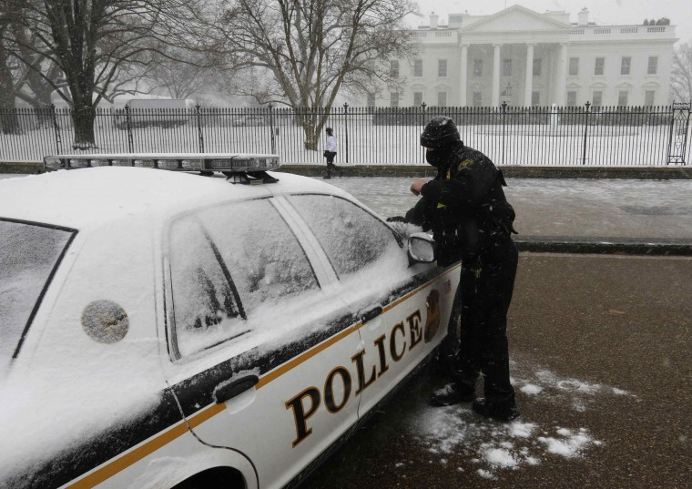 A member of the U.S. Secret Service Uniformed Division brushes snow off his vehicle in front of the White House in Washington during a snowstorm January 21, 2014. (Larry Downing/Reuters)