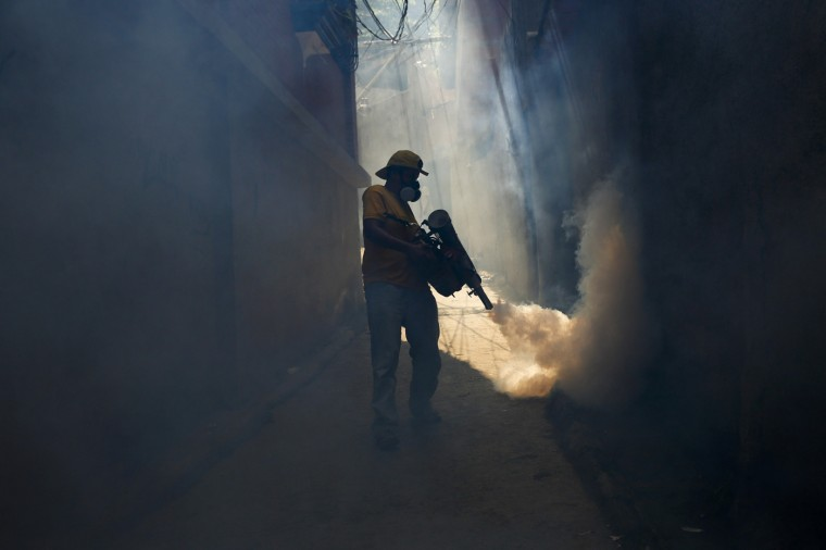 A worker from the municipality of Sucre carries out fumigation to help control the spread of Chikungunya and dengue fever, which are caused by viruses carried by mosquitoes, in the Petare slum district of Caracas September 22, 2014. Medical shortages have complicated Venezuela's efforts to treat outbreaks of mosquito-borne fevers, creating long lines at pharmacies to buy analgesics and leaving the ill without ways to control the swelling joints and aching bones that the disease causes. Venezuela has South America's highest incidence of chikungunya, a virus of African origin whose name comes from a Tanzanian term for being doubled-over in pain. It also has the fourth-highest incidence of dengue on the continent this year. (Carlos Garcia Rawlins/Reuters)